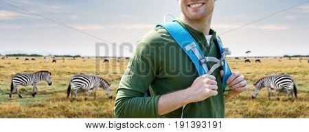 travel, tourism and people concept - close up of happy young man with backpack over african savannah and zebras background