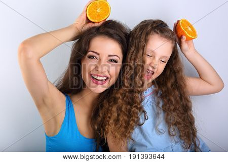 Grimacing Joying Humor Young Mother And Cute Long Hair Daughter Holding Slices Of Fresh Bright Orang