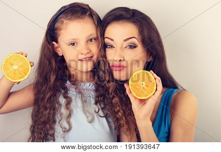 Grimacing Humor Young Mother And Cute Long Hair Daughter Holding Slices Of Fresh Bright Oranges In T