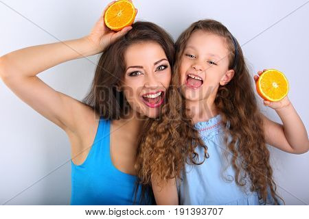 Grimacing Joying Fun Young Mother And Cute Long Hair Daughter Holding Slices Of Fresh Bright Oranges