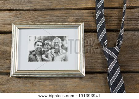 Overhead view of picture frame by necktie on wooden table
