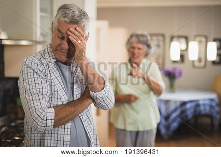 Angry senior woman yelling on senior man at home