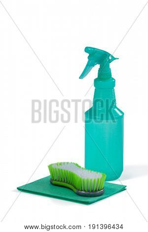 Detergent spray bottle and scouring pad on white background