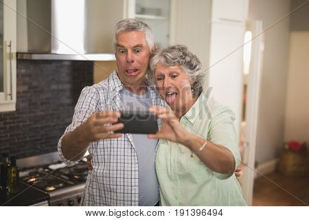 Mischievous senior couple taking selfie in kitchen at home