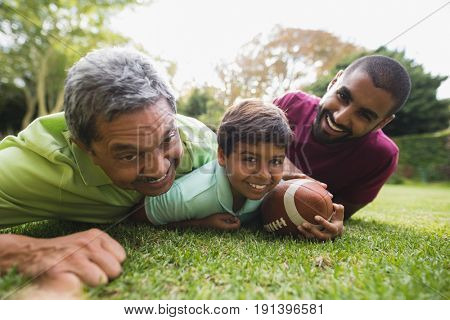 Portrait of multi generation family playing rugby at park