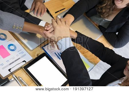young asian businessman joining united hand team of business people touching hands together after complete a deal in meeting - unity harmony teamwork partnership collaboration corporate concept.