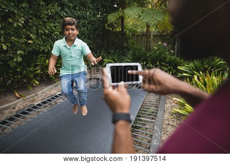 Cropped image of father photographing son while jumping on trampoline at park