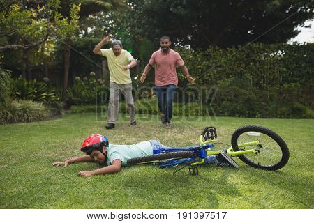 Grandfather and father running towards fallen boy with bicycle at park