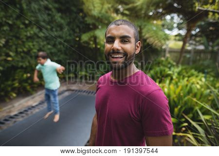 Portrait of smiling father while son jumping on trampoline at park