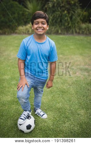 Portrait of smiling boy standing with soccer ball on field at park