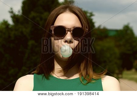 Young pretty girl chews a gum, outdoor