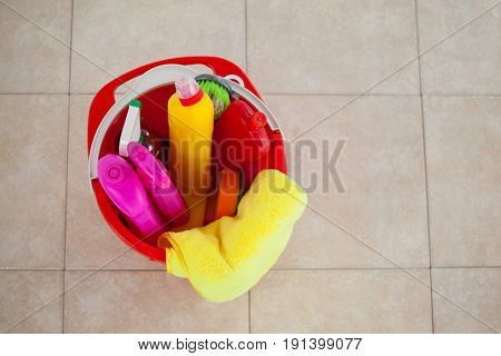 Close-up of bucket with cleaning supplies on tile floor