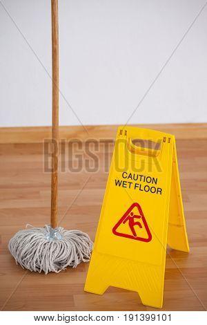 Mop with wet floor caution sign on wooden floor