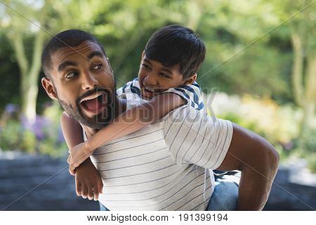 Happy young father piggybacking his son at porch