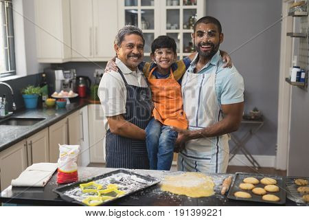 Portrait of happy multi-generation family standing together in kitchen at home