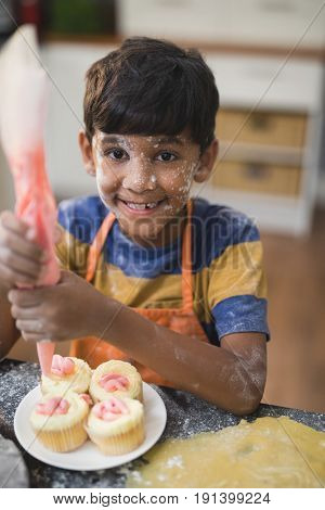 Portrait of happy boy making cup cakes in kitchen at home