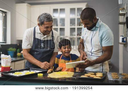 Happy multi-generation family using digital tablet while preparing food together in kitchen at home