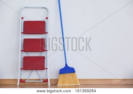 Ladder and sweeping broom leaning on white wall