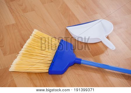 Close-up of sweeping broom and dustpan on wooden floor