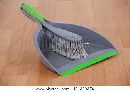 Close-up of dustpan and sweeping brush on wooden floor