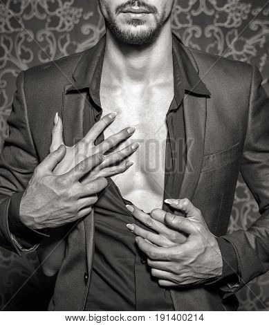 Sexy stylish rich man undressed by woman hands closeup black and white