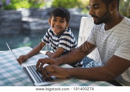 Portrait of smiling boy sitting by his father using laptop on table at porch