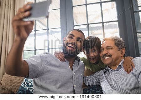 Smiling multi-generation family making face while taking selfie together at home