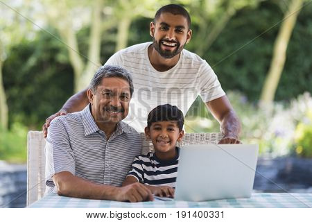 Portrait of happy multi-generation family using laptop together on table at porch