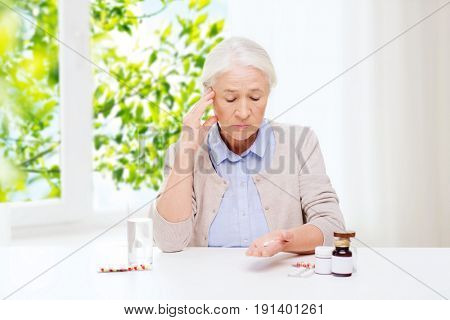 age, medicine and healthcare concept - senior woman with pills and glass of water at home over green natural background
