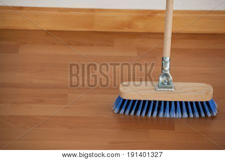 Close-up of sweeping broom with wooden handle on floor