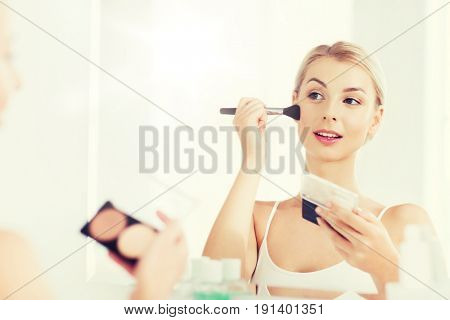 beauty, make up, cosmetics, morning and people concept - young woman with makeup brush and contouring and highlighting palette looking to mirror at home bathroom