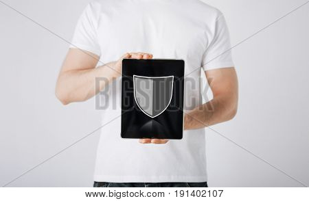 people, internet security and cyber protection concept - close up of man with virtual antivirus program shield icon on tablet pc computer screen over gray background