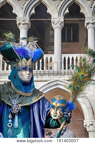 VENICE, ITALY - FEBRUARY 8, 2015: Costumed people in Venetian mask on the Piazza San Marco during Venice Carnival in Venice, Italy.