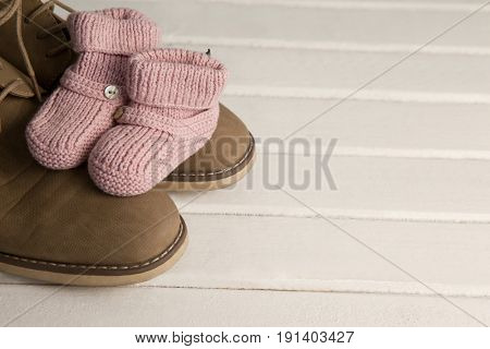 Close-up of pairs of child and fathers shoes on wooden plank