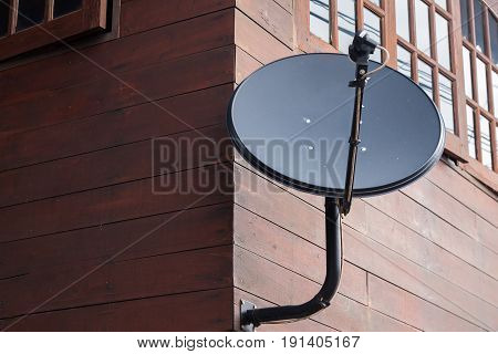 Black Satellite Dish Is Attached To The Wall Of The House.