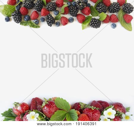 Ripe strawberries raspberries blueberries blackberries mint and basil leaves. Berries at border of image with copy space for text. Background berries. Top view. Various fresh summer berries on white background.