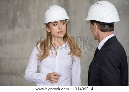 Serious Blonde Engineer In Hard Hat Looking At Colleague At Construction Site