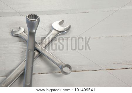 Close-up of wrenches on wooden plank
