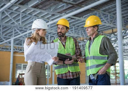 Serious inspector holding blueprint and looking at workers in hard hats