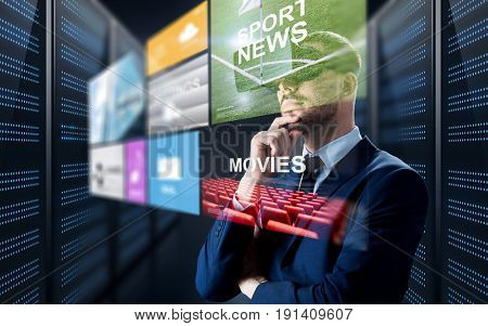 business, people and technology concept - businessman in virtual reality headset with multi media projection over futuristic server room background