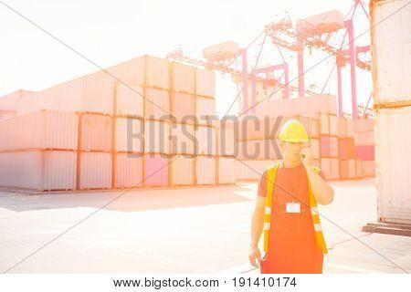 Mid adult man using walkie-talkie in shipping yard