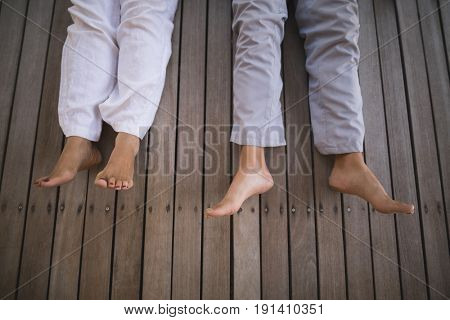 High angle low section of senior couple lying on wooden floor at porch