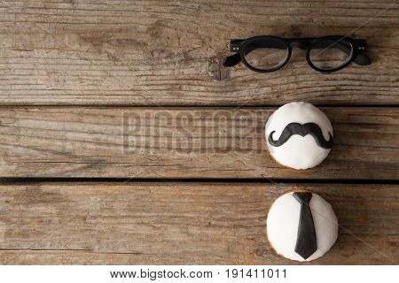 Close-up of delicious creative cupcakes and spectacles on wooden plank