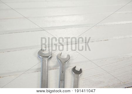 Close-up of wrenches arranged on wooden plank