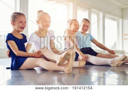 Smiling Girls Having Fun On Floor Of Ballet Class