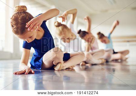 Girls Bending Sitting On Floor In Ballet Class