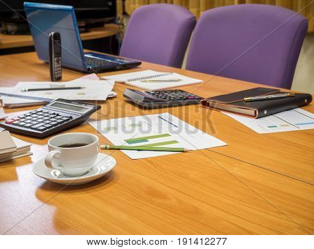 A Cup Of Coffee And Office Supplies In Meeting Room