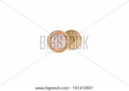 One Euro Coin Stand In Front Of The One Pound Coin On White Background