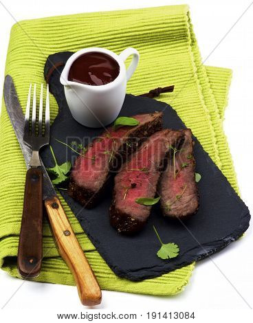 Slices of Delicious Roast Beef Medium Rare on Slate Serving Board with Tomato Sauce Fork and Table Knife closeup on Green Napkin