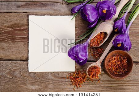 Crocus Flowers And Spoon With Soffron  Near Empty Card For Your Text On Wooden Background